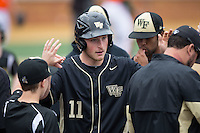 Jonathan Pryor (11) of the Wake Forest Demon Deacons high fives teammates after scoring a run against the Miami Hurricanes at Wake Forest Baseball Park on March 22, 2015 in Winston-Salem, North Carolina.  The Demon Deacons defeated the Hurricanes 10-4.  (Brian Westerholt/Four Seam Images)