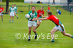 Padraig Slattery of Ballyduff off load the ball under pressure from Ronal Clifford of St Michaels Foilmore in the County Senior football league.