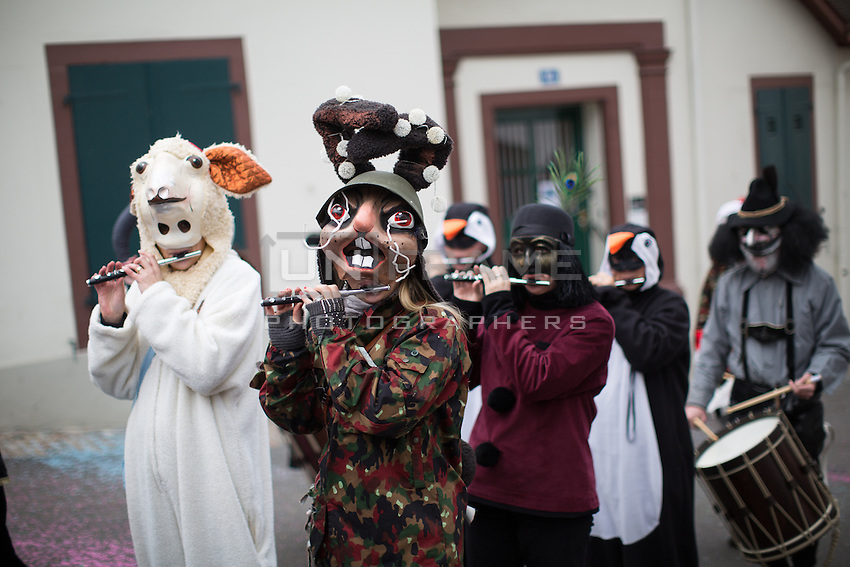 A 'clique' marches as they play traditional 'Gugge' music with piccolos and drums, along a route in the old town of Basel on the second day of Fasnacht in Basel, Switzerland. Feb. 24, 2015.