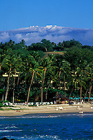 Beautiful blue ocean water and sky of Mauna Kea beach with palm trees and the Mauna Kea Observatories with snow on the summit in the back ground