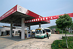 A tour bus stopped at a gas station above the town of Zigui China