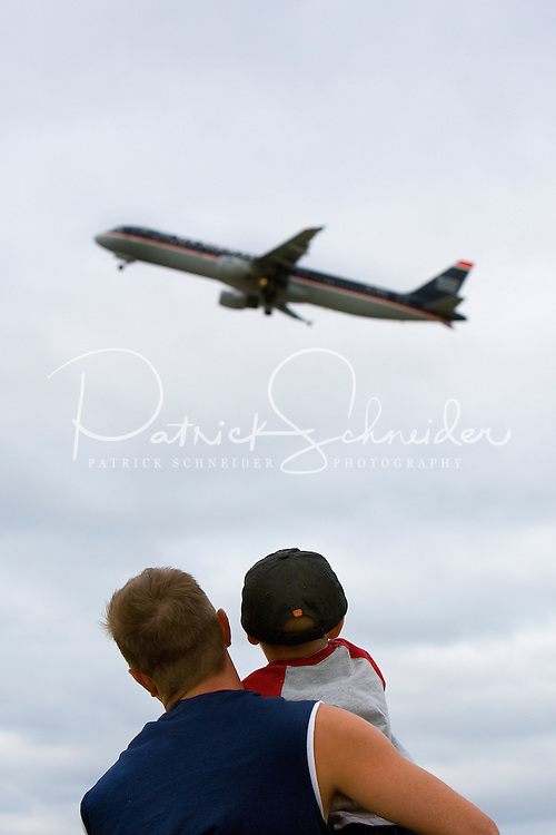 A father and son watch arriving and departing planes from a park near Charlotte-Douglas International Airport. The park, off Old Dowd Road, provides benches and picnic tables from which people can watch planes as they come and go. ..Charlotte-Douglas International Airport, one of US Airways' largest hubs, serves 10 major airlines, including Air Canada, Air Tran, American, Continental, Delta, JetBlue, Lufthansa, Northwest and United. The airport is the nation?s 10th largest in terms of total operations, the 18th largest in terms of total passengers and the 37th largest in terms of cargo. Charlotte-Douglas serves 640 daily flights, including direct flights to 120 cities. ..Photographer has series of images from Charlotte-Douglas International Airport, including aerials. ... PATRICK SCHNEIDER PHOTO.COM