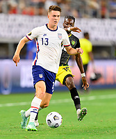 DALLAS, TX - JULY 25: Matthew Hoppe #13 of the United States brings the ball up the field in front of Blair Turgott #15 of Jamaica during a game between Jamaica and USMNT at AT&T Stadium on July 25, 2021 in Dallas, Texas.