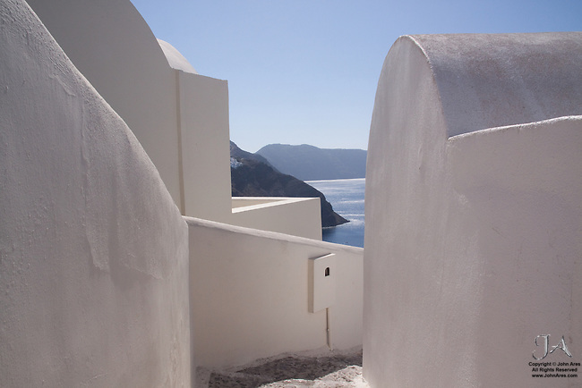 Winding labyrinth of Greek buildings leads to the cliff of the caldera in Oia.