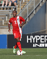 Belize midfielder David Trapp (2) brings the ball forward.  In CONCACAF Gold Cup Group Stage, the national team of Cuba (white) defeated national team of Belize (red), 4-0, at Rentschler Field, East Hartford, CT on July 16, 2013.