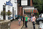 Balcombe West Sussex UK. Local residents chat in the village outside the Balcombe Stores and the village pub The Half Moon Inn.