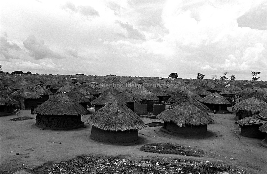 An overview of Pabbo Internally Displaced PeopleÕs (IDP) camp. Pabbo is the largest IDP in Uganda, holding an estimated 63,000 people. The IDP camps of Northern Uganda formed when areas in the region became unsafe for civilians to live. Clean water, sanitation, food, employment, education, moral living, and human rights have almost been entirely depleted. Furthermore, congestion within the camps has contributed to major health and living problems. With 1.6 Ð 2 million people displaced and with an almost total lack of resources to care for them, the local peopleÕs very existence physically, emotionally and culturally is at stake. The war between the LordÕs Resistance Army and the Ugandan military has been transpiring since 1986. Thousands have been killed and abducted. Pabbo, Gulu District, Uganda, Africa. July 2004 © Stephen Blake Farrington