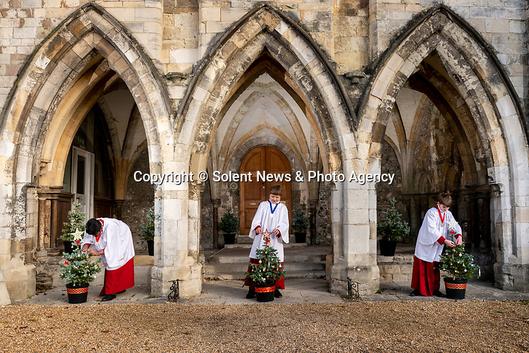 Pictured: Choristers of Winchester Cathedral Choir add the finishing touches to small Christmas trees beneath the arches of the Deanery as Christmas decorations are installed around Winchester Cathedral, which opened for public service to visitors today, December 2nd. <br /> <br /> During the second coronavirus lockdown in England the Cathedral remained open for private prayer and reflection, and after a month-long nationwide lockdown ended today Winchester will enter Tier 2 in the new system implemented by the government to curb the spread of the coronavirus pandemic.<br /> <br /> © Jordan Pettitt/Solent News & Photo Agency<br /> UK +44 (0) 2380 458800