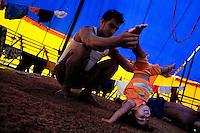 A little Colombian girl does gymnastics (handstand) with help of his father at the Circo Anny, a family run circus wandering the Amazon region of Ecuador, 4 July 2010. The Circo Anny circus belongs to the old-fashioned traveling circuses with a usual mixture of acrobat, clown and comic acts. Due to the general loss of popularity caused by modern forms of entertainment such as movies, TV shows or internet, these small family enterprises balance on the edge of survival. Circuses were pushed away and now they have to set up their shows in more remote villages. The circus art and culture is slowly dying.