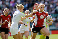 Mandy Marchak of Canada breaks through the tackle of Michaela Staniford (left) and Joanne Watmore of England during the iRB Challenge Cup at Twickenham on Sunday 13th May 2012 (Photo by Rob Munro)