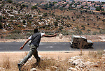 Palestinian youths throw stones at an Israeli military vehicle during a protest against the construction of the West Bank separation barrier in the village of Nilin near Ramallah on July 8, 2009. Photo by Issam Rimawi