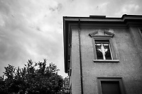 Switzerland. Canton Ticino. Lugano. Private house with a swiss flag in the window. The flag of Switzerland displays a white cross in the centre of a square red field. The white cross is known as the Swiss cross. 6.06.2020 © 2020 Didier Ruef