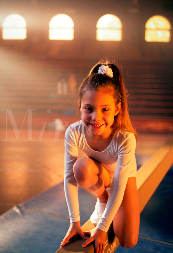A smiling young girl gymnast poses on a balance beam in a gym.