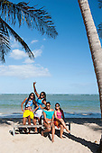 Itaparica Island, Bahia State, Brazil. Four young smiling women, all shapes and sizes, with sunglasses at the beach.