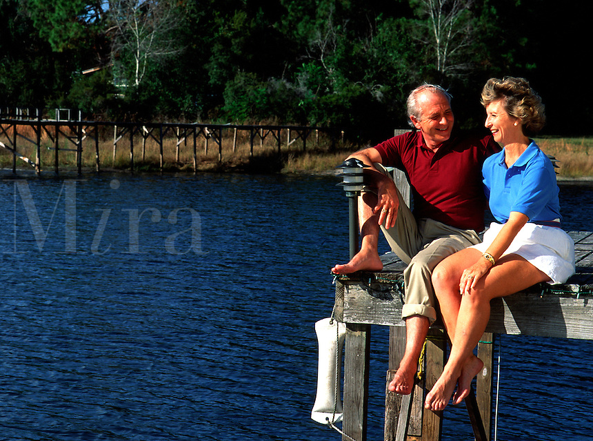 A smiling mature couple relax and talk as they sit on a dock by a lake.
