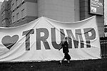 "MIDDLETOWN, PA — SEPTEMBER 26, 2020:  A person walks past a ""Love Trump"" sign outside of a rally for President Donald Trump during the Covid-19 pandemic at the Harrisburg International Airport on September 25, 2020 in Middletown, PA.  Thousands of attendees, most of whom were maskless, rode on shuttle busses to and from the long term parking lot and the event site— as the world nears one million Covid-19 deaths— defying the states ban on gatherings over 250 people.  Photograph by Michael Nagle"