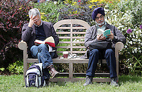 Monday 26 May 2014, Hay on Wye, UK<br /> Pictured: Two men on a bench reading books on the green.<br /> Re: The Hay Festival, Hay on Wye, Powys, Wales UK.