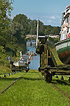Sailing boat on cable car being pulled uphill while contrary cradle with tourist ship going downhill. Ostroda - Elblag Canal: Overland transportation of boats on rail cars at the Elblag Canal (Polish: Kanal Elblaskie, German: Oberlaendischer Kanal), Masuria, Poland, Europe. No releases available. ---Info: A system of rail-mounted cable trolleys on skipways and traditional locks are connecting the various sections of the Elblag Canal. A 100 metre difference in water levels is overcome during a length of 80 km between Ostroda and Elblag. The rail lift devices are mechanically driven by water power.--- HISTORY: The canal was designed in 1825-1844 by Georg Steenke, carrying out the commission given by the king of Prussia. Construction began in 1844. As the route was not important enough to justify building expensive, traditional locks between lakes, an ingenious system of tracks was employed instead, though the canal includes a few locks as well. Built originally under the name Oberländischer Kanal (Overland Canal) and situated in the Kingdom of Prussia, it was opened in 1860. Since 1945 the canal has been located in Poland. After wartime damage was repaired, it was restored to operation in 1948. Today it is used mainly for recreational purposes. It is considered one of the most significant monuments related to the history of technology on the territory of modern Poland..