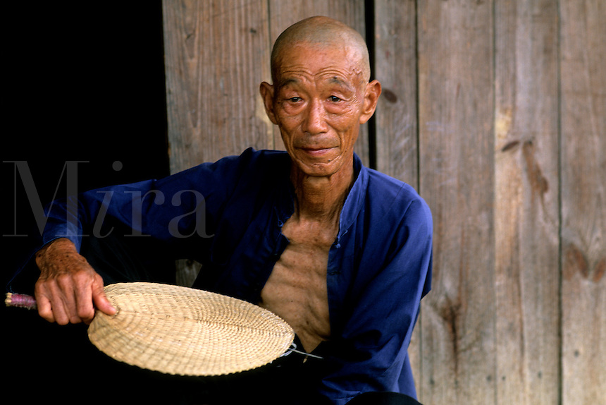 Colorful portrait of old man on Fan Li River in Guilin China.