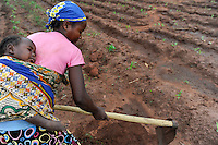 ANGOLA Kwanza Sul, rural development project, village Catchandja, woman prepares the field / Afrika ANGOLA Kwanza Sul, laendliches Entwicklungsprojekt ACM-KS, Dorf Catchandja, landwirtschaftliche Beratung und Verbesserung der Anbaumethoden, Vergabe von Saatgut, Frau mit Baby hackt ihr Feld