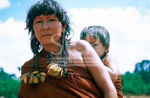 Ipixuna Village, Brazil. Arawete Indian woman wearing home woven wrap and feather hair adornments with her baby on her back.