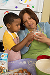 3 year old boy at home with mother, learning to cook