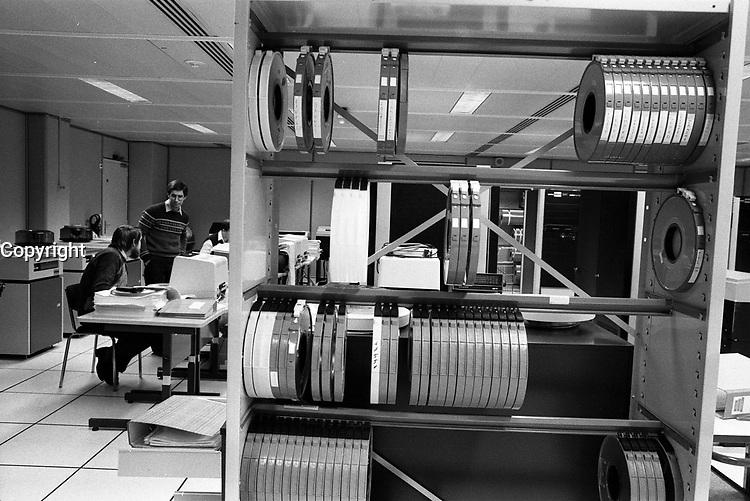"""Dans les locaux du CNES (Centre National d'Etudes Spatiales). 11 mars 1985. Vue d'ensemble des locaux du CRIS (Centre de Rectification des Images Spatiales) : au 1er plan étagères à bobines ; en arrière-plan personnel devant leurs écrans. Cliché pris le jour où le satellite Spot 1 subit toutes une série de tests aux vibrations (visite des locaux et installations). Observation: Satellite Spot 1 : plus gros satellite européen construit pour observer la Terre (images à haute résolution). Maîtrise d'oeuvre CNES. Intégration par Matra. Alcatel-Thomson Toulouse a fourni des équipements. Projet né en 1975 au CNES ; phase de réalisation a commencé en juin 1980. Mise en orbite prévue en octobre 1985 par Ariane 1. Création en parallèle de la société """"Spot-Images"""" chargée de prospecter et de commercialiser le produit à l'échelle mondiale."""