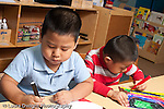 Education prechool 3-4 year olds handedness two boys using opposite hands (right hand, left hand) while drawing with markers