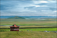A Tibetan temple sits on a hilltop against a vast space of grassland.
