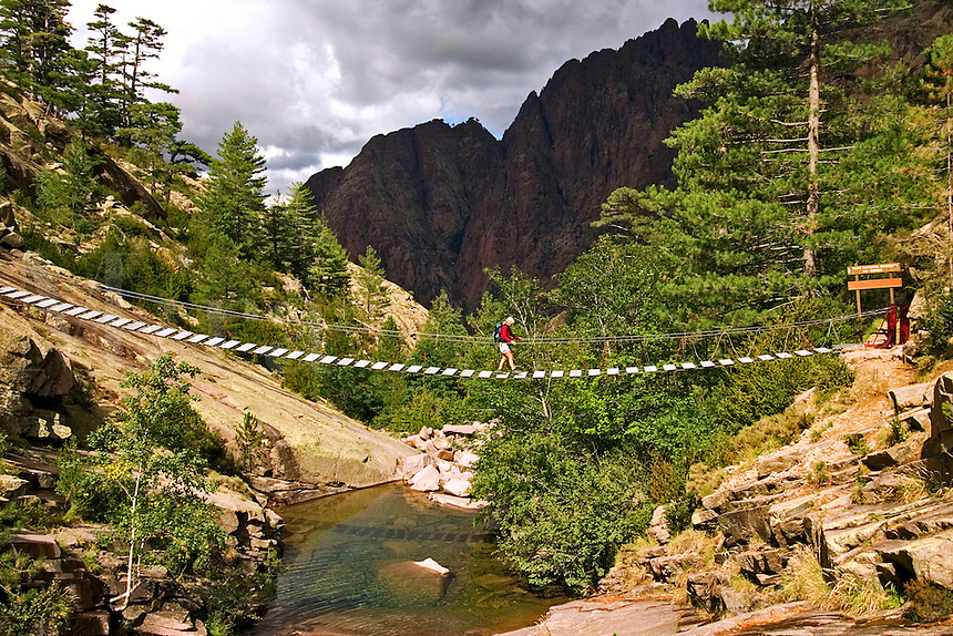Corsica. Balagna. Hiker on the bridge at Spasimata, near Bonifatu, on the GR20 long distance walking track.  France..
