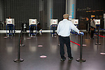 BROOKLYN, NY — OCTOBER 24, 2020:  A poll worker wearing gloves rests a hand on a stanchion inside the Barclay's Center, during the first day of early voting in the U.S. Presidential Election, on October 24, 2020 in Brooklyn, NY.  Photograph by Michael Nagle