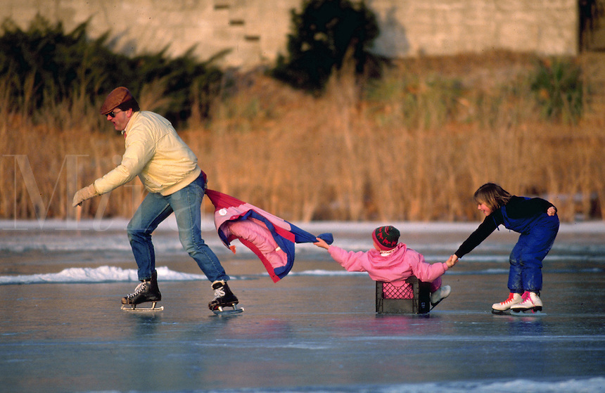 A father and daughters ice skating. parent, parents, child, children, sports, family activities, fun.