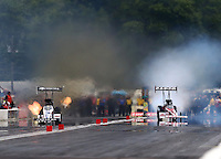 Aug 17, 2014; Brainerd, MN, USA; NHRA top fuel dragster driver Morgan Lucas (left) takes the win over a tire smoking Steve Torrence during the Lucas Oil Nationals at Brainerd International Raceway. Mandatory Credit: Mark J. Rebilas-