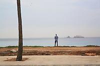 Senegal. Dakar. A single man looks at the Madeleine islands and the Atlantic ocean. 08.12.09 © 2009 Didier Ruef