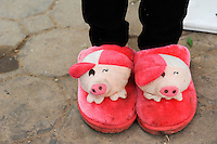 LAO PDR Oudomxay, chinese woman with pig slippers at market