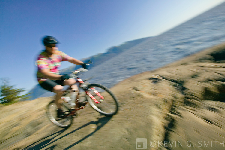 Middle aged man, caucasian, riding a mountain bike on the rocks along the shoreline, blurred motion, Turnagain Arm, summer, Kenai mountains in the background, Southcentral Alaska, USA. MR.