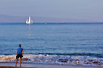 A young woman looks wistfully out to sea from a Maui beach as a sailboat cruises by the Hawaiian island of Lanai.