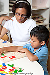 Education Preschool 3-5 year olds female teacher working with boy on counting numbers puzzle vertical