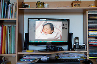 The photograph on the computer in Sophie Serrano's lounge shows Manon, her daughter, when she was one day old, Thorenc, France, 11 November 2013. Manon, born on the 4th July 1994, was accidentally switched with another baby at the maternity clinic 5 days after she was born. Manon's true identity wasn't discovered until 2004 and she, like the baby she was swapped with, has stayed with the family that raised her. This photograph was taken before the swap by Manon's biological parents.
