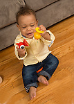 10 month old baby boy sitting and banging wooden toy pieces together