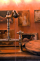 Close-up of the kitchen tap with a series of small nudes on the wall behind