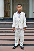 Snappily dressed young wedding guest, on the steps of the main cathedral in Ambon City. The 1999-2002 religious war between Maluku's Christian and Muslim populations, mainly centred on Ambon Island, led to over 5000 deaths and to around 500,000 people become displaced. Destroyed homes and offices, churches and mosques are slowly being either torn-down or renovated.  Urban centres, such as Ambon City, continue to be split along largely sectarian lines, and tensions are never far below the surface. Riots between Christian and Muslim youths erupted in September 2011 and, most recently, June 2012, though luckily simmered down just as quickly, partly due to community leaders learning how to defuse tensions from the earlier, more devastating, conflagration. /Felix Features