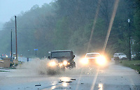 Motorists navigate flood water and debris during heavy rain on Wednesday April 28 2021 along Arkansas 12 in the Prairie Creek community east of Rogers. Go to nwaonline.com/210429Daily/ to see more photos.<br /> (NWA Democrat-Gazette/Flip Putthoff)