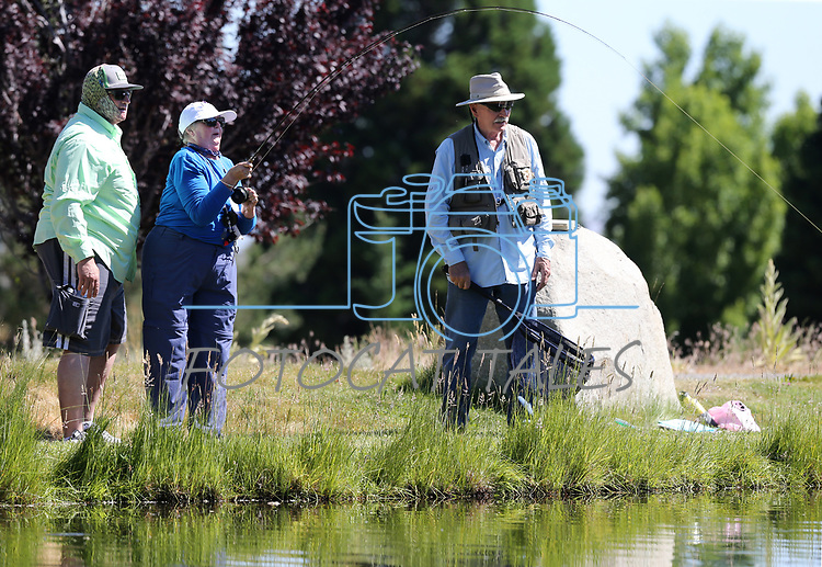 Jon Blakely, left, and George Liddell watch as breast cancer survivor Peggy Limi, of Bakersfield, reels in a fish during a Casting for Recovery retreat in Gardnerville, Nev., on Friday, June 30, 2017. The nationwide program, hosted locally with Carson Tahoe Cancer Center, pairs cancer survivors with fly-fishing guides.   <br /> Photo by Cathleen Allison/Nevada Photo Source