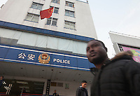 An African man walks past a police station in an area of Guangzhou known to locals as 'Chocolate City', Guangzhou, Guangdong Province, China, 08 December 2014. The health authorities of Guangzhou are said to be stepping up their monitoring of the African community in light of the ongoing outbreak of the Ebola virus disease in West Africa.