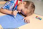 Education preschool 3-4 year olds art activty boy drawing letters with marker horizontal holding marker in fist grip leaning head close to paper