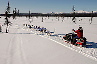Sunday  March 14 , 2010   Gerald Sousa sits on his sled and uses ski poles as he runs down a swamp 2 miles after leaving the the Kaltag checkpoint with the Nulato Hills in the background .