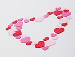 Heart shape arranged with pink, red and white hearts on white background