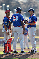 Auburn Doubledays pitching coach Franklin Bravo #34 talks with catcher Wilfri Pena #16 and Manny Rodriguez #22 during a game against the Batavia Muckdogs at Dwyer Stadium on July 17, 2011 in Batavia, New York.  Batavia defeated Auburn 8-3.  (Mike Janes/Four Seam Images)