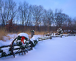 Bureau County, IL <br /> Bureau County, IL <br /> Snow cover on a split rail fence and wagon wheels near prairie grasses and the bare trees of a winter forest